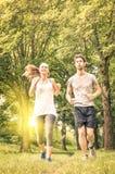 Couples heureux pulsant et fonctionnant en parc - concept de forme physique Image libre de droits