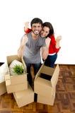 Couples heureux rapprochant une nouvelle maison déballant des boîtes en carton Photo libre de droits