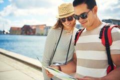 Couples heureux recherchant des directions sur une carte Photo stock