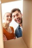 Couples heureux regardant à l'intérieur de la boîte images stock