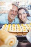 Couples heureux regardant des pâtisseries par le verre Images libres de droits