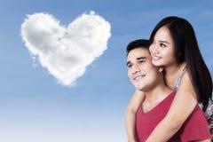 Couples heureux regardant l'amour de nuages Photographie stock