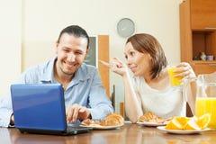 Couples heureux regardant l'email dans l'ordinateur portable pendant le petit déjeuner Photographie stock libre de droits