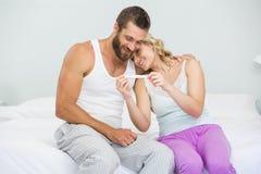 Couples heureux regardant l'essai de grossesse sur le lit photos libres de droits