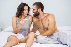 Couples heureux regardant l'essai de grossesse sur le lit photographie stock libre de droits