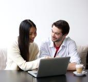 Couples heureux regardant l'ordinateur portatif Photos stock