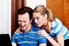 Couples heureux regardant l'ordinateur portatif Photos libres de droits