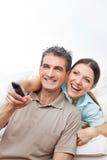 Couples heureux regardant la TV Photo libre de droits