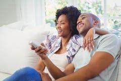 Couples heureux regardant la TV Images stock