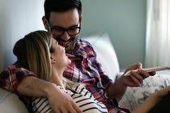Couples heureux regardant la TV dans leur maison Image libre de droits