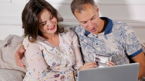 Couples heureux regardant le balayage de bébé image stock