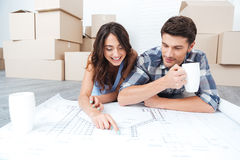 Couples heureux regardant le plan de maison de construction images stock