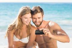 Couples heureux regardant le smartphone Image libre de droits