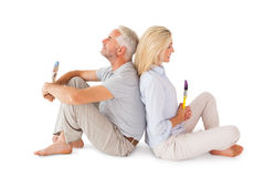 Couples heureux reposant et tenant des pinceaux Photographie stock libre de droits