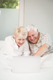 Couples heureux riant tout en à l'aide de l'ordinateur portable dans le lit Photos libres de droits