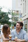 Couples heureux riant tout en buvant du café froid au café de trottoir Photographie stock libre de droits