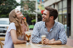 Couples heureux riant tout en se reposant au café de trottoir Photos stock