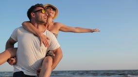 Couples heureux riants appréciant Sunny Weather près de la mer Homme fort tenant son amie sur les épaules sur le bleu banque de vidéos