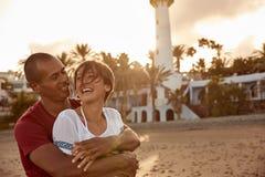 Couples heureux riants sur la plage Photographie stock