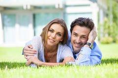 Couples heureux s'étendant dans le jardin Images stock
