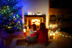 Couples heureux s'étendant par une cheminée dans un salon confortable le réveillon de Noël Photographie stock