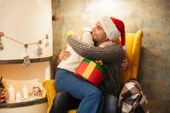 Couples heureux s'étreignant après échange de cadeau tandis que sittin Images libres de droits