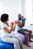 Couples heureux s'exerçant avec des haltères sur la boule de forme physique dans la chambre à coucher Images stock
