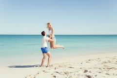 Couples heureux sautant des vacances de plage Photographie stock
