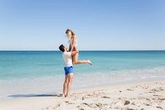 Couples heureux sautant des vacances de plage Photos libres de droits