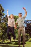 Couples heureux sautant en parc Photos stock