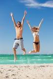 Couples heureux sautant sur la plage Images libres de droits