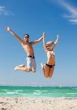 Couples heureux sautant sur la plage Photo libre de droits