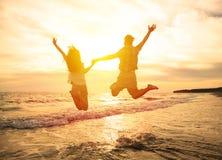 Couples heureux sautant sur la plage Photos libres de droits