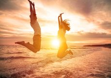 Couples heureux sautant sur la plage Photo stock