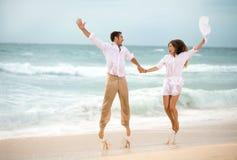 Couples heureux sautant sur la plage Images stock