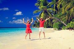 Couples heureux sautant sur la plage d'été Images libres de droits