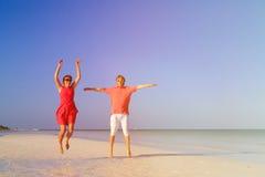 Couples heureux sautant sur la plage d'été Photos stock