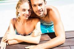 Couples heureux se penchant sur le bord de piscine Photos libres de droits