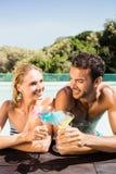 Couples heureux se penchant sur le bord de piscine et grillant avec des cocktails Photos stock