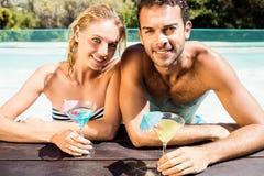 Couples heureux se penchant sur le bord de piscine et tenant des cocktails Photographie stock libre de droits