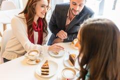 Couples heureux se reposant à la table avec leur ami commun dans un café à la mode Photo libre de droits