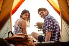 Couples heureux se reposant à la tente de camping Photos stock