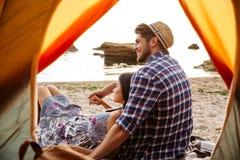 Couples heureux se reposant à la tente de camping Images libres de droits