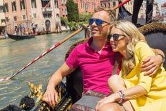 Couples heureux se reposant dans la gondole leurs vacances photographie stock