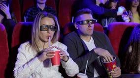 Couples heureux se reposant dans la salle de cin?ma, film 3D de observation, mangeant du ma?s ?clat?, souriant banque de vidéos