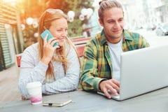 Couples heureux se reposant dans le café de rue ensemble, la femme parlant au téléphone et l'homme à l'aide de l'ordinateur porta Photos libres de droits