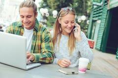 Couples heureux se reposant dans le café, la femme parlant au téléphone et l'homme de rue à l'aide de l'ordinateur portable Images stock