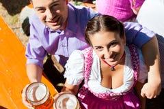 Couples heureux se reposant dans le jardin de bière Image libre de droits