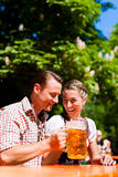 Couples heureux se reposant dans le jardin de bière Photo stock