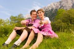 Couples heureux se reposant dans le pré alpestre Photos stock